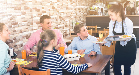 Female is bringing salad and juice to young visitors of family cafe.