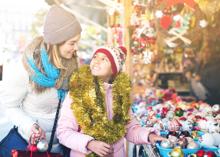 Smiling little girl with happy mom buying decorations for Xmas. Focus on girl Stock Photo