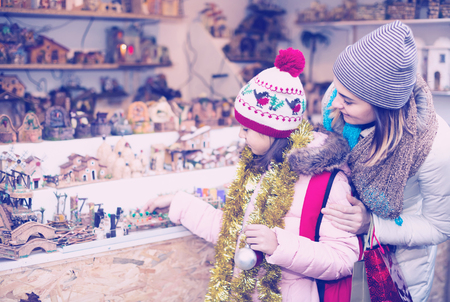 figurines: positive female customers staring at counter of kiosk with figures for creating  miniature Christmas scenes