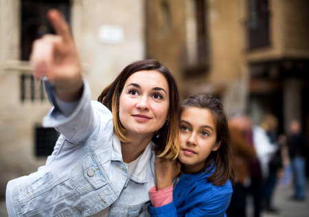 Glad mother and daughter pointing at sight during sightseeing tour. Focus on the woman Stock Photo