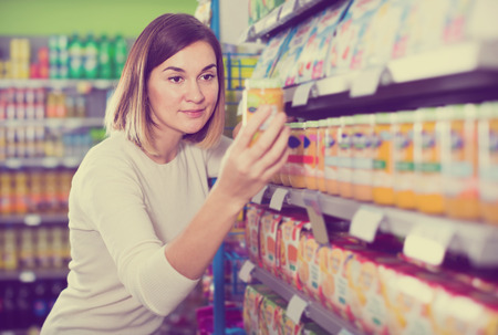 smiling girl customer looking for tasty baby food in supermarket