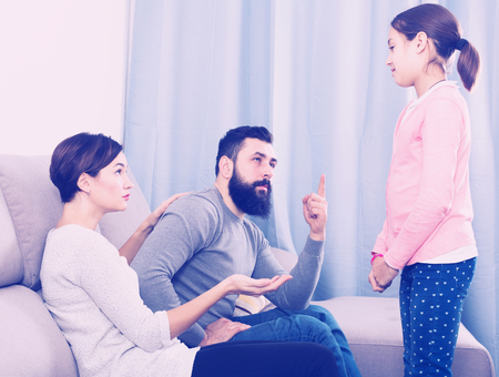 Young man and woman lecturing their daughter for bad behavior at home Stock Photo