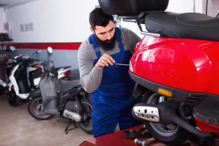 garage: Smiling male worker fixing failed scooter in motorcycle workplace