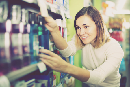 smiling girl customer looking for effective mouthwash from shelves in supermarket