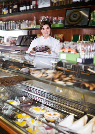 Smiling assistant helping to choose dessert in confectionery