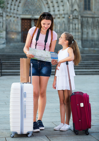 Young happy cheerful  mother with little girl travelling together searching location on paper map
