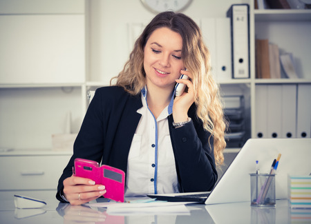 Portrait of female working in office and talking on the phone