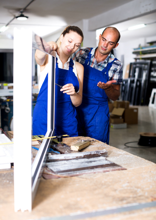 Young female assembler of metal-plastic windows consulting with master in assembly shop Stock Photo