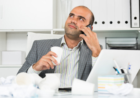 Portrait of male working in office and talking on the phone Фото со стока