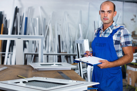 Efficient positive focused workman in overalls controlling quality of assembly of plastic window in workshop Stock Photo