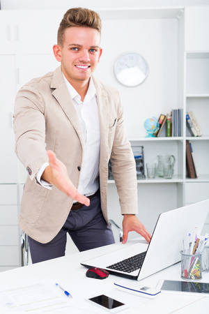 Smiling adult business partner welcoming somebody at desk in office Stock Photo
