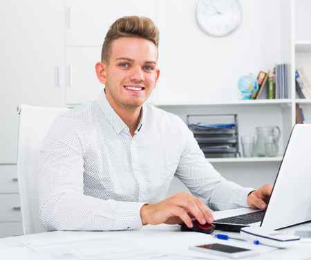 Happy young man working with papers and laptop in office Stock Photo