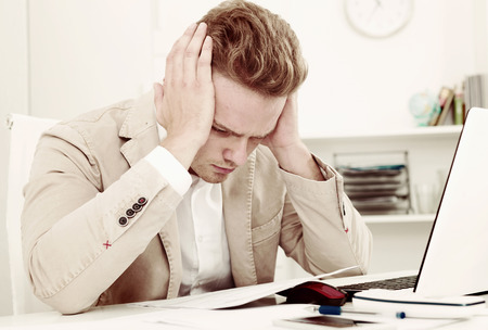 Frustrated young man having business problems with papers at workplace