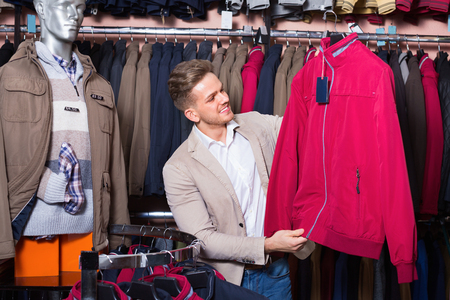 Cheerful positive guy deciding on warm coat in men's cloths store Stock Photo