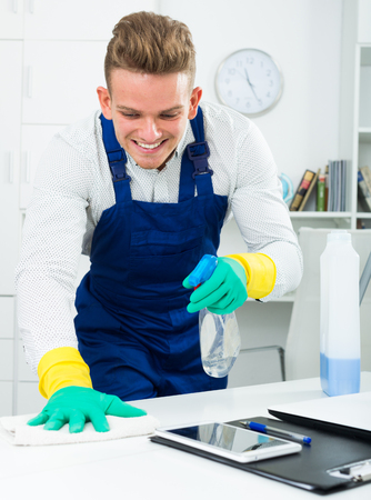 Positive man in overall with supplies doing professional clean-up Stock Photo