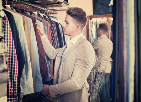 Young man choosing new shirt in men's clothes store