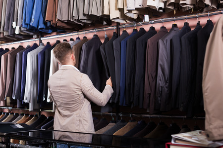 Positive guy deciding on new suit in men's cloths store