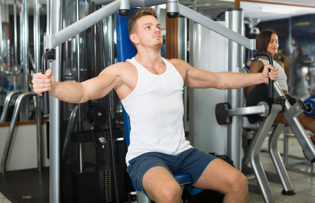 strong young man training upper body using fly machine in gym