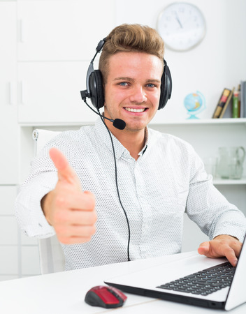 Happy man with headset and laptop  showing thumbs up