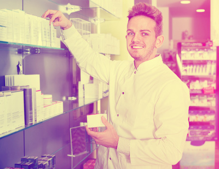 Happy glad male pharmacist wearing white coat standing among shelves in drug store