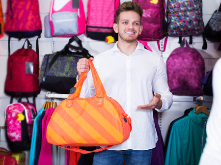 Young couple choosing new sports bag in sports store
