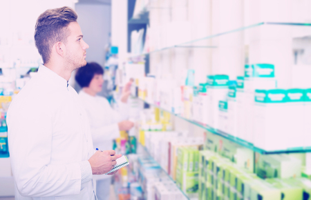Portrait of glad man druggist in white coat giving advice to customers in pharmacy Stock Photo