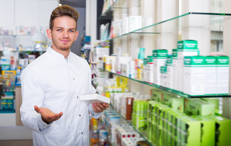 Adult pharmacist wearing white coat standing among shelves in drug store Stock Photo