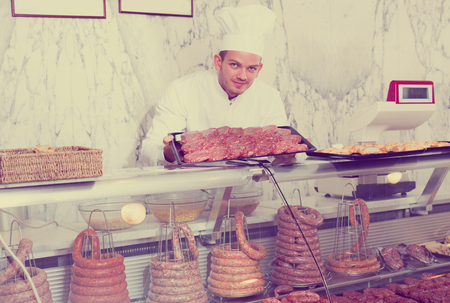 Cheerful shop-boy in working clothes taking raw meat from stall