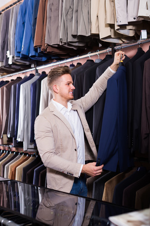 happy male customer examining suits in men's cloths store