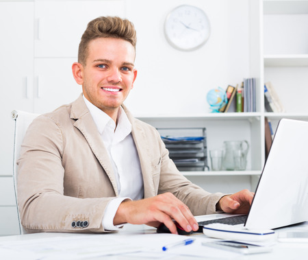 friendly smiling  young manager working efficiently at office desk with laptop