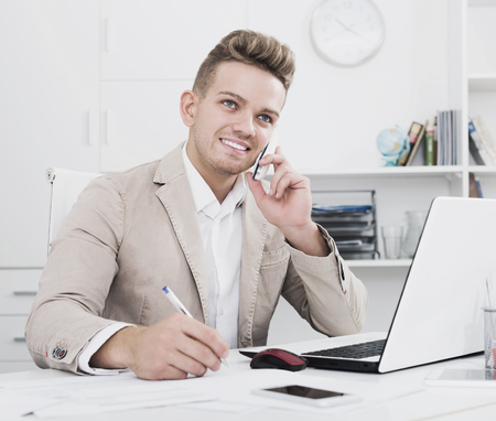 Handsome positive young man having mobile conversation in modern office