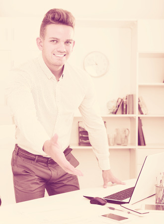 Young business partner welcoming somebody at desk in office Stock Photo