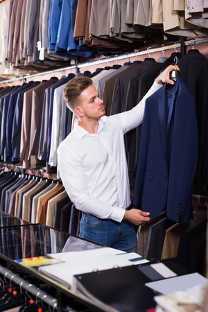 serious male customer examining suits in men's cloths store