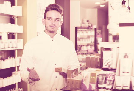 Cheerful pharmacist wearing white coat standing among shelves in drug store
