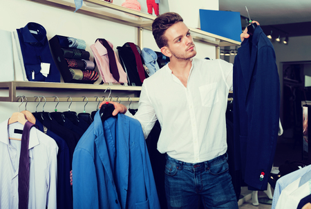 Young positive man choosing jacket at clothing shop Stock Photo