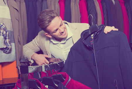 Glad male customer examining coats in men's cloths store Stock Photo