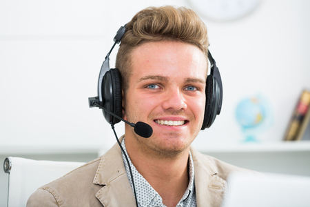 Portrait of young and successful call centre operator in office Stock Photo