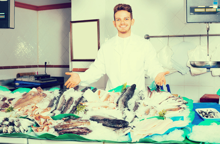 Smiling seller posing near display with cooled fish and seafood Stock Photo