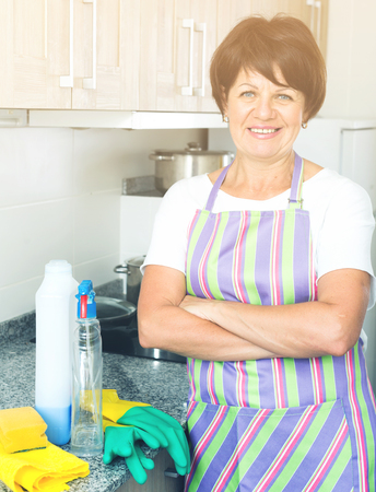 mature cheerful woman cleaning surfaces and kitchen in apartment