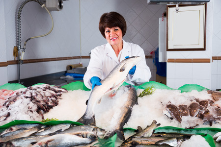 european seller with apron offering fresh fish in shop Stock Photo