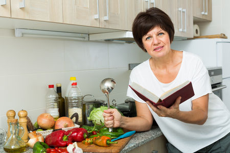 Portrait of glad mature woman checking recipe while preparing soup in cooking pot on kitchen at home