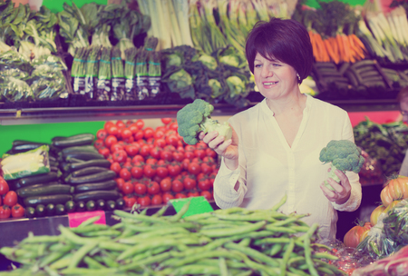 Middle aged smiling woman choosing vegetables on the marketon the market Stock Photo