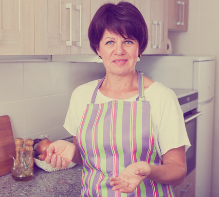 cheerful senior woman standing against kitchen interior background