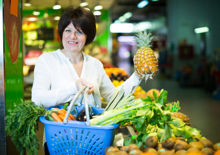 Adult cheerful female taking fruits with basket on the market Stock Photo