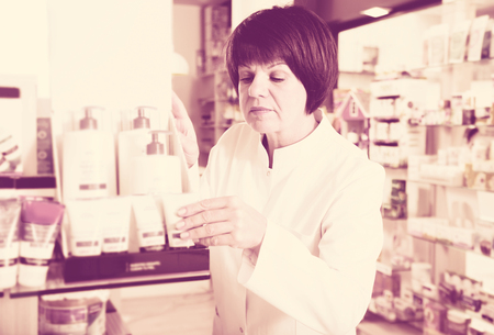 Glad woman druggist wearing white coat standing among shelves in drugstore