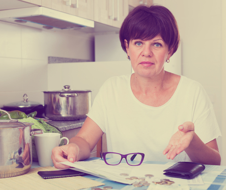 portrait of sad mature woman thinking how to pay bills on her kitchen
