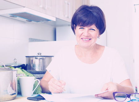 portrait of smiling senior woman bookkeeping bills and payments at her kitchen Stock Photo