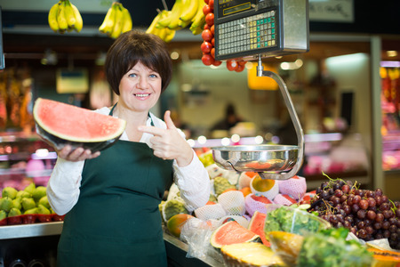 Middle aged woman selling watermelon and other fruits on the store Stock Photo