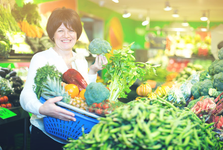 Adult cheerful female taking vegetables with basket on the market Stock Photo