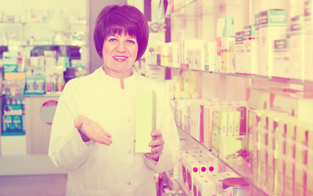 caucasian woman pharmacist wearing uniform and working in pharmaceutical shop Stock Photo